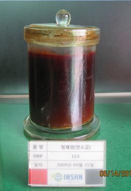 Nádoba se solným roztokem běžné kuchyňské soli. Armatura v této tekutině není vůbec vidět, je naprosto zřetelná koroze.